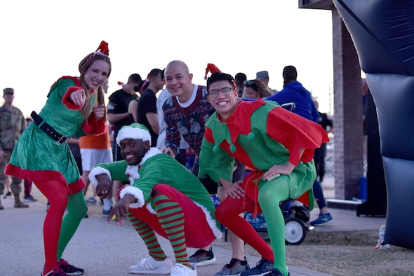 Col. Andres Nazario, 17th Training Wing commander, poses with participants in the Jingle Bell 5K held on Goodfellow Air Force Base, Texas, Dec. 6, 2019. Members were able to participate in the run before the rest of the events at the Christmas Tree Lighting ceremony. (U.S. Air Force photo by Senior Airman Seraiah Wolf)