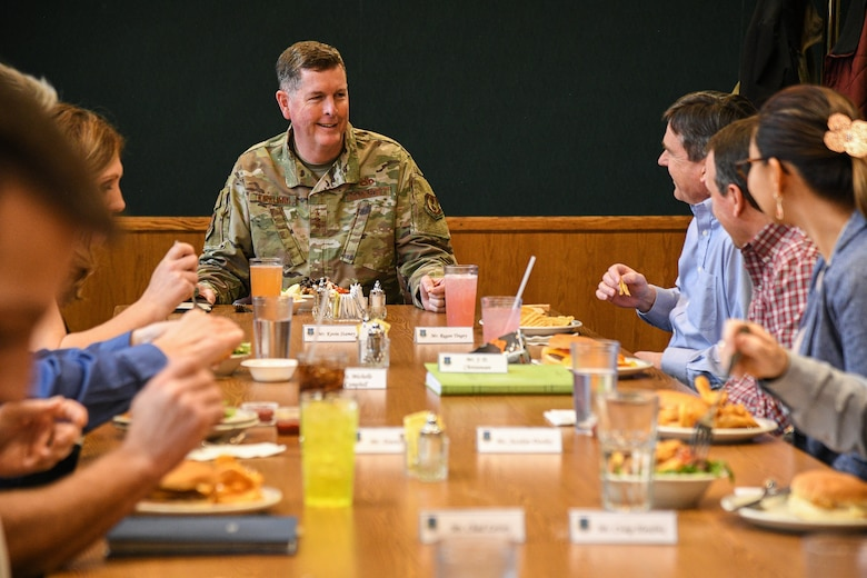 Lt. Gen. Gene Kirkland interacts with several squadron-level leaders gathered at a table eating lunch.