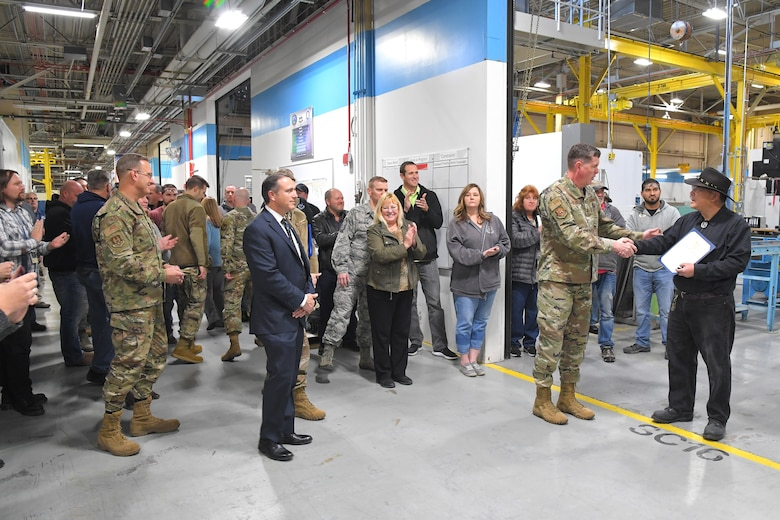 Lt. Gen. Gene Kirkland shakes hands with employee Matthew Yun, 581st Missile Maintenance Squadron, to recognize him for 40 years of federal service in the bay of maintenance warehouse while several other employees and guests watch the presentation.