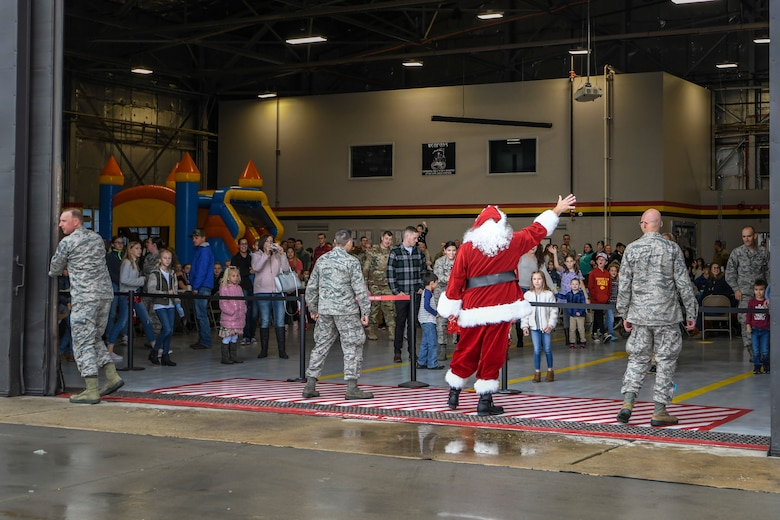 """Santa waves to members of the 419th Fighter Wing and their families after """"arriving"""" in an F-35 Lightning II"""