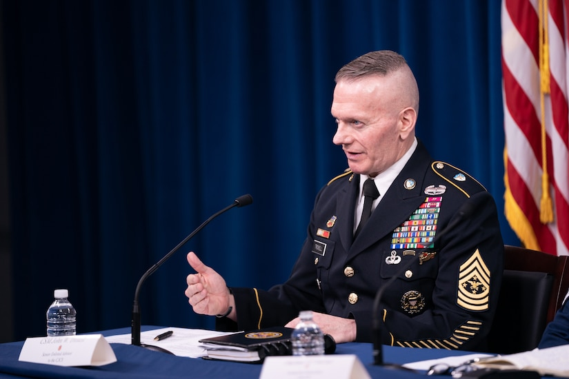 A uniformed service member sits behind a table and speaks into a microphone.