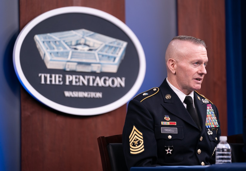 "A uniformed service member sits behind a table and speaks into a microphone. Behind him, a sign on the wall reads ""The Pentagon - WASHINGTON."""