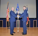"""Col. James """"J.C."""" Miller, 433rd Operations Group commander, hands the 733rd Training Squadron's guidon to Lt. Col. Seth W. Asay signifying the transition of command Dec. 7, 2019 at Joint Base San Antonio-Lackland, Texas. The 733rd TRS is responsible for the formal training unit student administration for initial and upgrade students on temporary duty in all C-5M crew positions (pilot, flight engineer, loadmaster). (U.S. Air Force photo by Master Sgt. Kristian Carter)"""