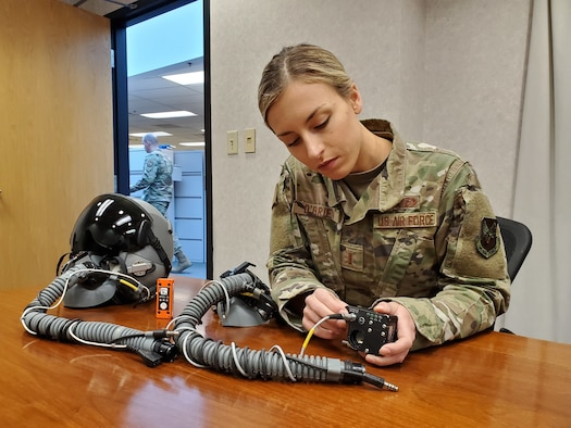"""2nd Lt. (Dr.) Dominique O'Brien, Project Lead, Airman Sensing and Assessment Product Line, with the 711th Human Performance Wing's Airman Systems Directorate, displays two devices her team used during flight tests in support of a request from the 20th Fighter Wing to provide assistance with assessing cabin pressure, oxygen concentrations, and possible hypoxia-like symptoms reported by their F-16 pilots. One device is called the """"Slam Stick,"""" (orange in color), which measures tri-axial acceleration – or acceleration in all three axes, X, Y, and Z. The second device is called the Insta Pilot Breath Air Monitor, or IPBAM, (black device being held by Lt. O'Brien) which measures several critical parameters of the breathing gas delivered to the pilot. (U.S. Air Force photo/Bryan Ripple)"""