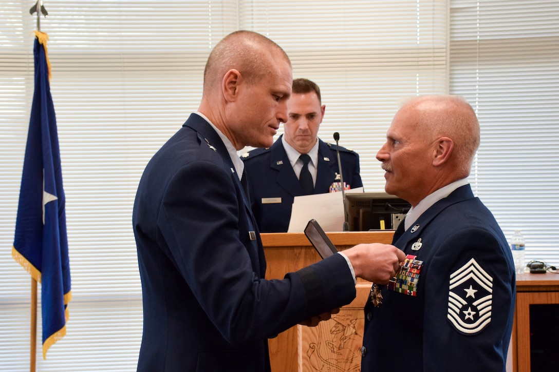 Brig. Gen. Shawn Ford (left), Deputy Adjutant General for Air, Iowa National Guard, presents Chief Master Sgt. Timothy E. Cochran (right), former Command Chief Master Sgt. (CCM) of the Iowa Air National Guard, with the Legion of Merit award during his retirement ceremony held in the dining facility of the 132d Wing in Des Moines, Iowa on Saturday, December 7, 2019.  Cochran is the 6th CCM of Iowa and has served the state and Air Guard for over thirty-eight years.  (Air National Guard photo by Tech. Sgt. Linda K. Burger/Released)