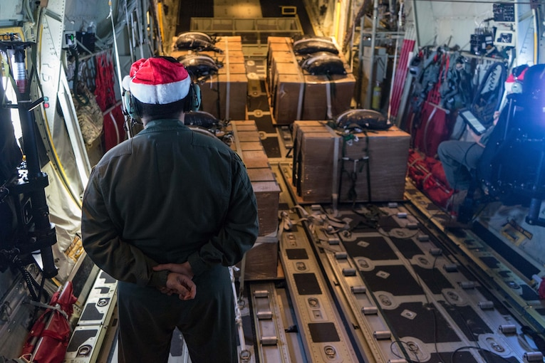 An airman wearing a Santa hat stands with his back to the camera in a military aircraft looking at a lot of boxes.