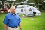 Man stands in front of helicopter.