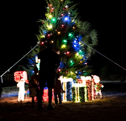 A family poses for personal photos at the 325th Force Support Squadron holiday tree lighting ceremony at Tyndall Air Force Base, Florida, Dec. 6, 2019. The event consisted of the base commander, Col. Brian Laidlaw, lighting the big tree and also included carols sung by the Mosley High School Choir, crafts, and a visit from Santa Claus. (U.S. Air Force photo by Staff Sgt. Magen M. Reeves)