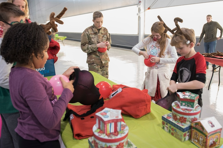 Children blow up balloons as part of the reindeer games competition during the 167th Airlift Wing family day event, Dec. 8, 2019