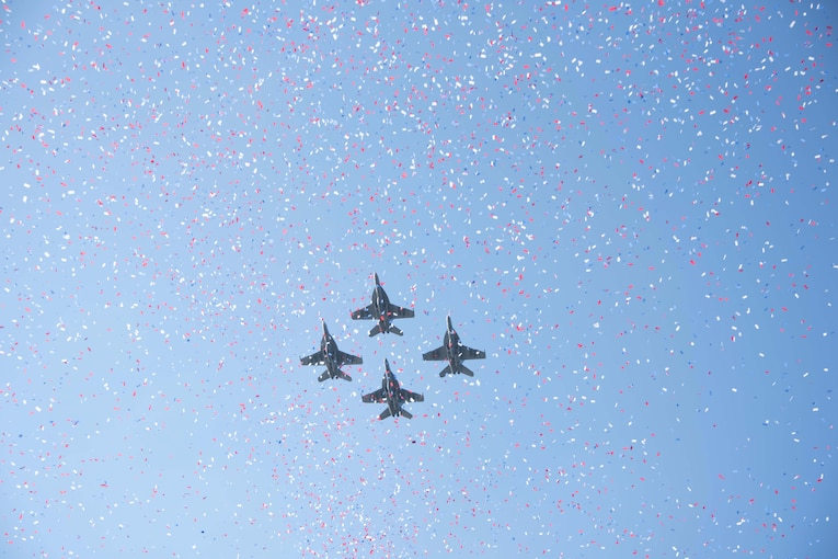 Four military jets fly through confetti against a blue sky.