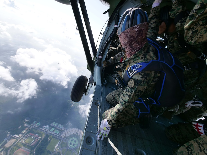 Person looks at parachutists from inside a helicopter.