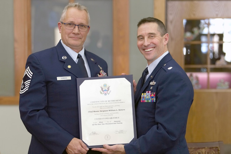 Lt. Col. Scott Uselding, 434th Force Support Squadron commander, presents Chief Master Sgt. Will Somers with his certificate of retirement at Grissom Air Reserve Base, Ind., Dec. 7, 2019. Somers hung up his uniform after 33 years of military service, but continues to serve Grissom as a civilian. (U.S. Air Force photo / Airman 1st Class Harrison Withrow)