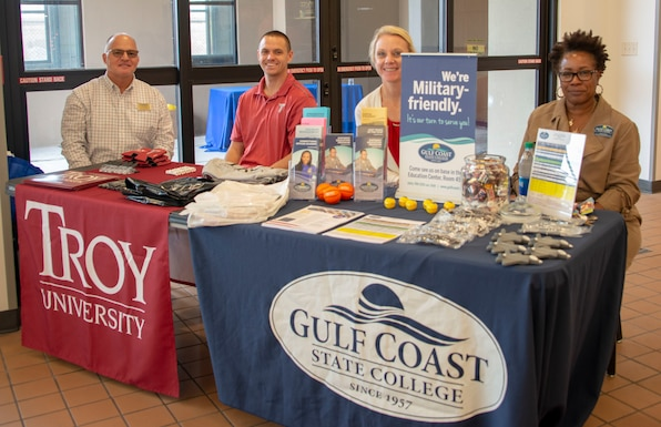 Representatives from the base education office, Troy University, Embry Riddle Aeronautical University, and Gulf Coast State College sit at the Base Exchange food court to answer questions and assist students with enrollment at Tyndall Air Force Base, Florida, Dec. 9, 2019. The 325th Force Support Squadron hosted the education outreach event to help current and prospective students navigate education benefits, on-base schools, and the variety of degree programs offered. (U.S. Air Force photo by 2nd Lt. Kayla Fitzgerald)