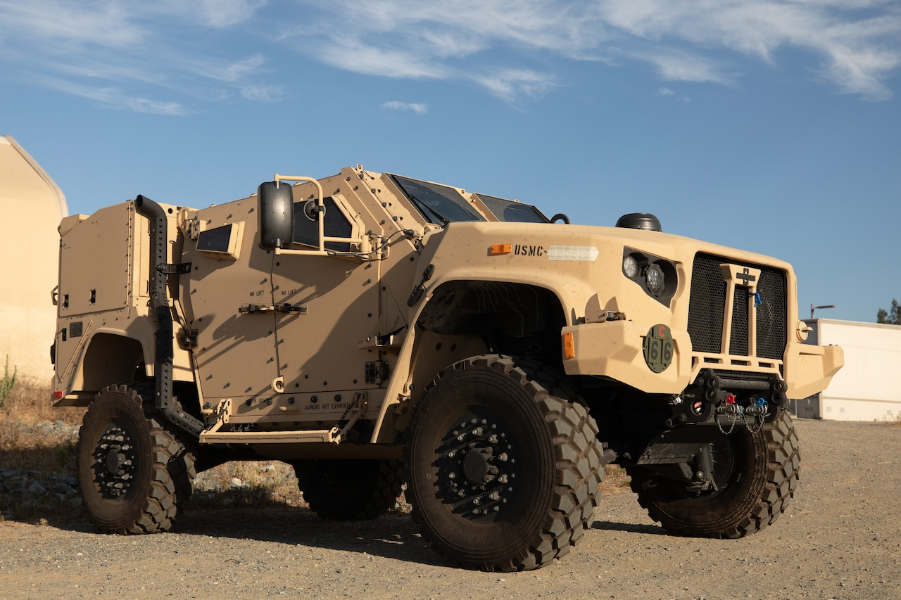 A military combat vehicle sits in a dirt lot.