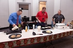 Operations Director Arthur Welsh (far right) watches as DLA Disposition Services Director Mike Cannon (center) and Chief of Staff Peter Foreman grill pancakes for the employees.