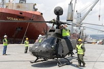 An OH-58D Kiowa Warrior helicopter, part of an Excess Defense Articles grant, is unloaded May 16 at the Greek port city of Volos.