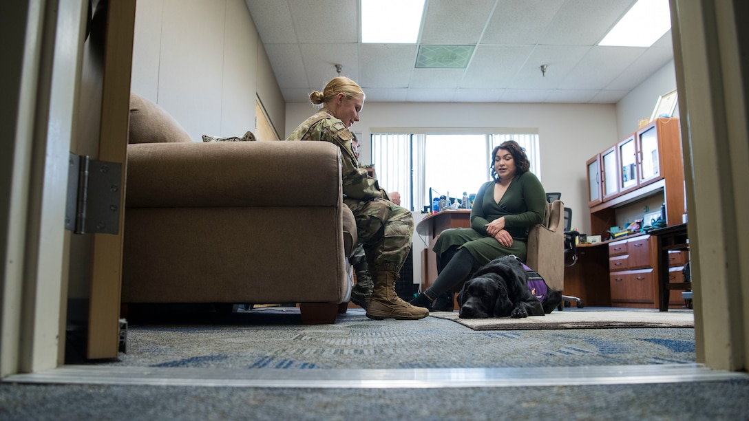 Teresa Loya, 30th Space Wing sexual assault prevention and response specialist, and Preston, 30th SW courthouse facility dog, meet with an Airman at Vandenberg Air Force Base, Calif., Dec. 4, 2019. Preston comes to work every day to the Sexual Assault Prevention and Response office, as he is a certified and highly trained courthouse dog who provides support to victims and witnesses. (U.S. Air Force photo by Airman 1st Class Aubree Milks)