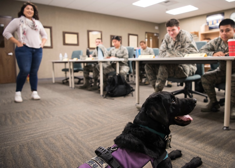 Teresa Loya, 30th Space Wing sexual assault prevention and response specialist, and Preston, 30th SW courthouse facility dog, brief the December First Term Airman class at Vandenberg Air Force Base, Calif., Dec. 4, 2019. Every month, members from the Sexual Assault Prevention and Response office brief FTAC and other service members with what their office does, as well as the services and resources that are available to them. (U.S. Air Force photo by Airman 1st Class Aubree Milks)