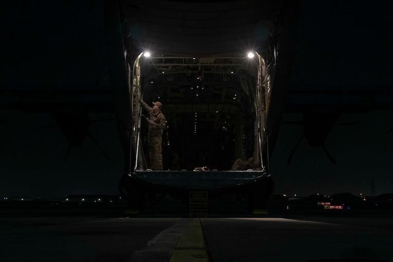 An airman stands inside of an aircraft at night.
