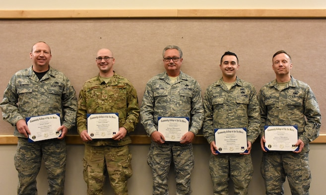 Community College of the Air Force graduates are photographed with their diplomas after a graduation ceremony at Whiteman Air Force Base, Mo., Dec. 8, 2019.