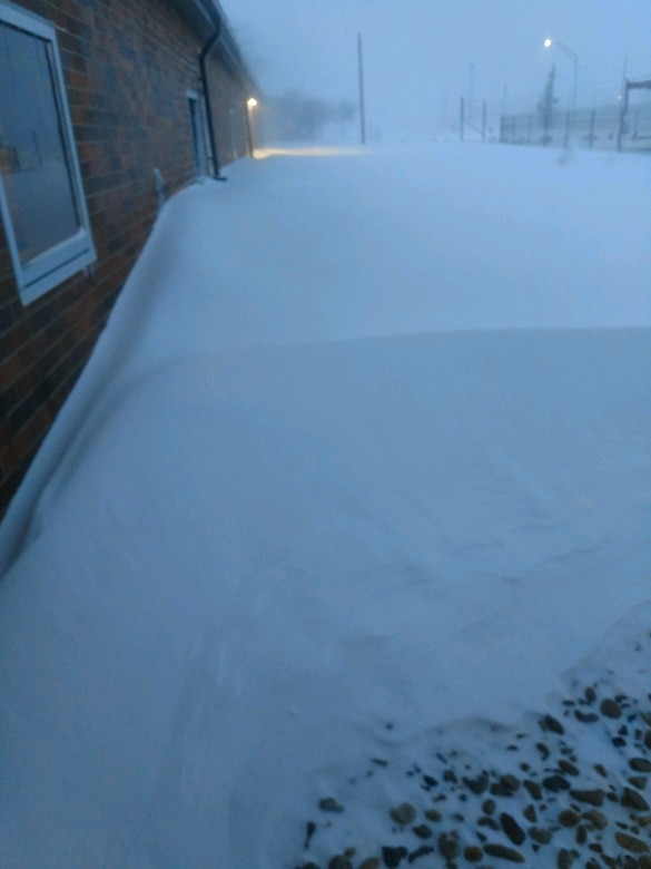 Snow is piled outside the door of a MQ-9 squadron building at Ellsworth Air Force Base.