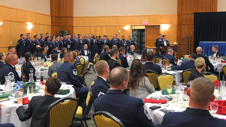 The graduates of Airman Leadership School Class 20-A pose for a group photo against ballroom wall while guests watch on from seated at a number of tables in the room.
