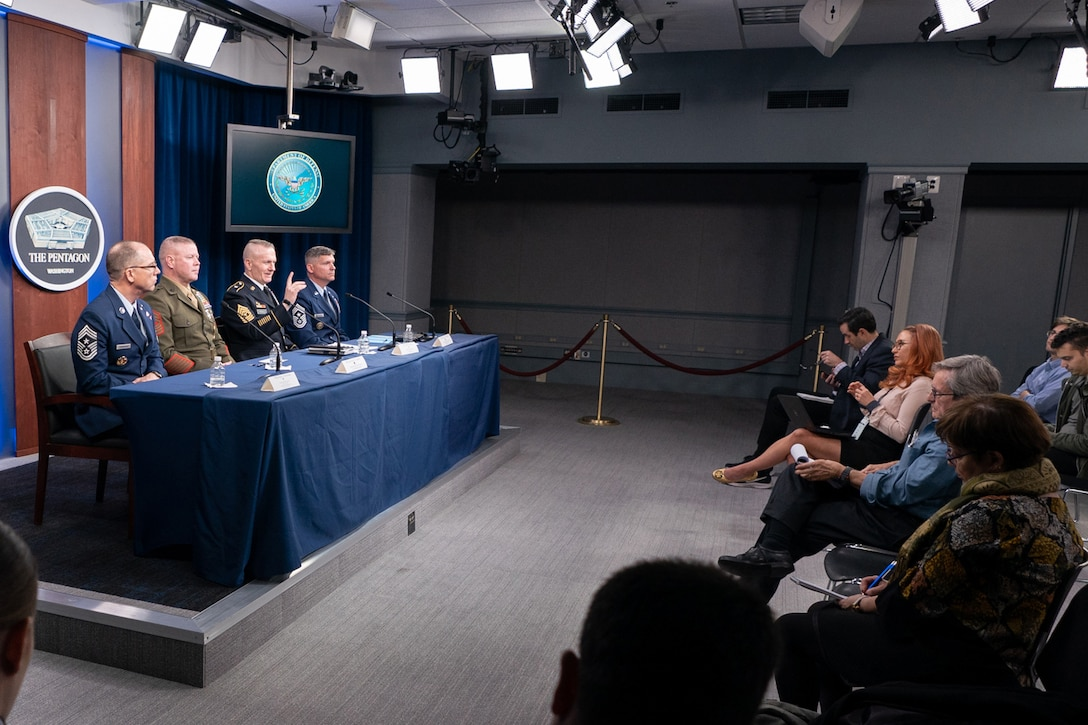 Four service members in uniform sit at a blue-draped table facing an audience of reporters.