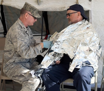 Lt. Col. Todd Welch, a physicians assistant, assigned tothe 149th Medical Group's Det. 1, simulates providing medical treatment to a role player during the Texas National Guard's 6th CERFP Task Force, which includes the 149th Fatality Search and Recovery Team, participated in a response evaluation exercise Dec. 7, 2019, in Round Rock, Texas.