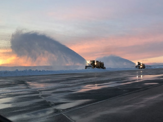 Two snow plows remove snow from a flightline during Sunset at Ellsworth Air Force Base.