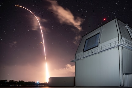 A long-exposure photograph of a night launch of a missile, which leaves a trail of light.