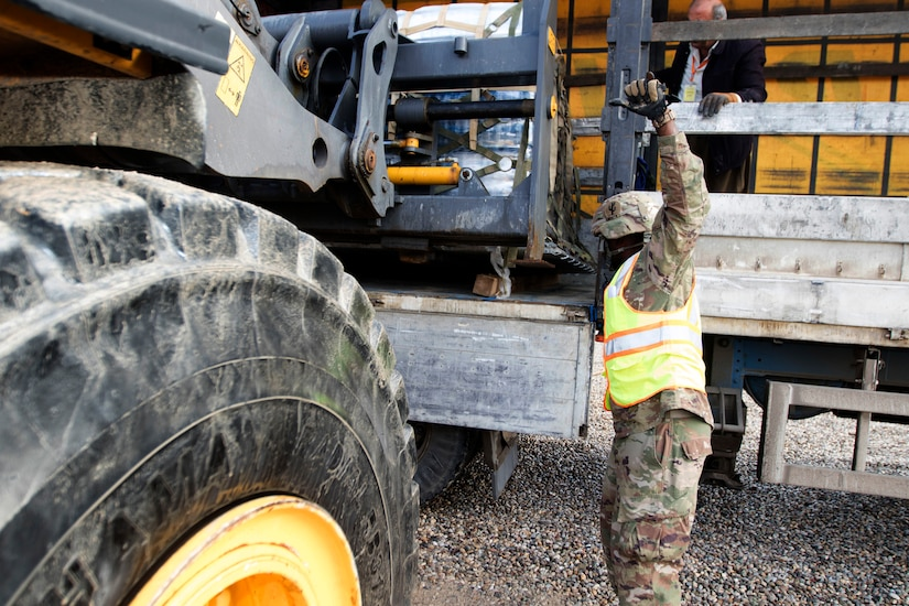 Spc. Desmond Smith, movement specialist, 941st Movement Control Team, works with a white truck driver to guide a forklift in loading a pallet of water at the Syrian Logistics Cell operations center, Erbil, Iraq, Dec. 3, 2019. Once loaded and secured in the truck, the water will be delivered to Syria.