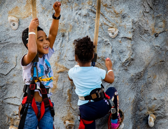 Members of the local and U.S. communities climb a rock wall during the 2019 Camp Courtney Festival on Dec. 7-8, Okinawa, Japan.