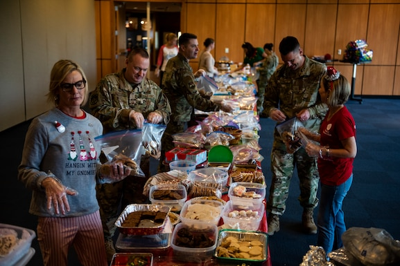 Airmen and first sergeants from the 325th Fighter Wing bag holiday cookies with members of the Tyndall Spouses Club at Tyndall Air Force Base, Florida, Dec. 9, 2019. The Tyndall Spouses Club and Tyndall First Sergeants held a Cookie Caper event, where they collected hundreds of donated cookies to distribute to Airmen living in the on base dormitories, as well as giving extra cookies to units and offices on base. The goal of the event was to take care of Airmen and to give back to those who serve the wing's mission. (U.S. Air Force photo by Staff Sgt. Magen M. Reeves)