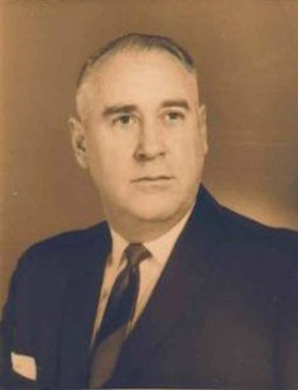 A man in a suit, tie and pocket square poses for an official photo.