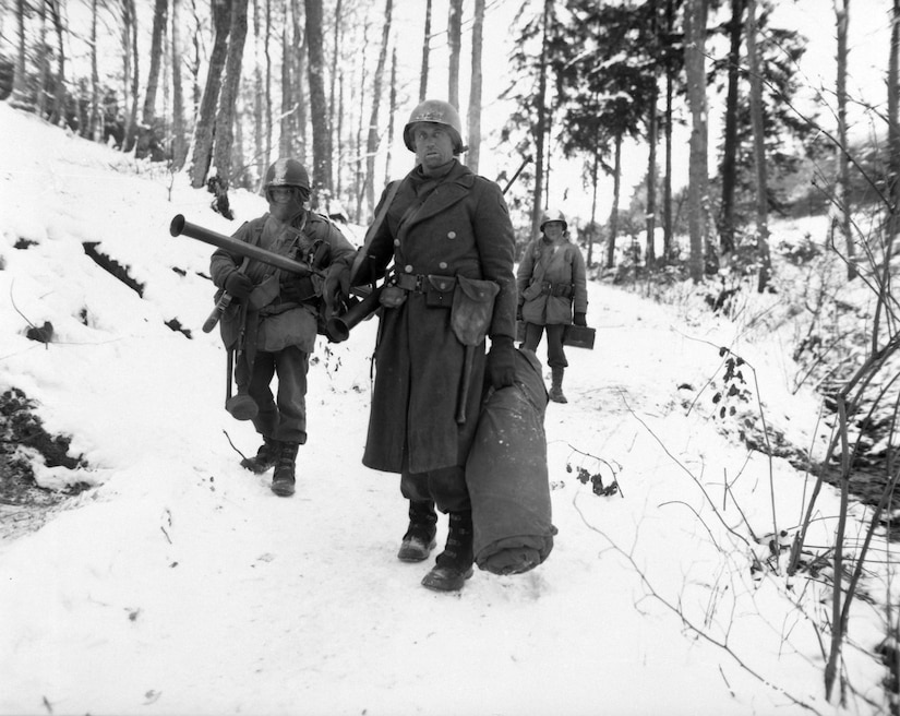 Three soldiers trudge through heavy snow in a forest carrying lots of equipment.