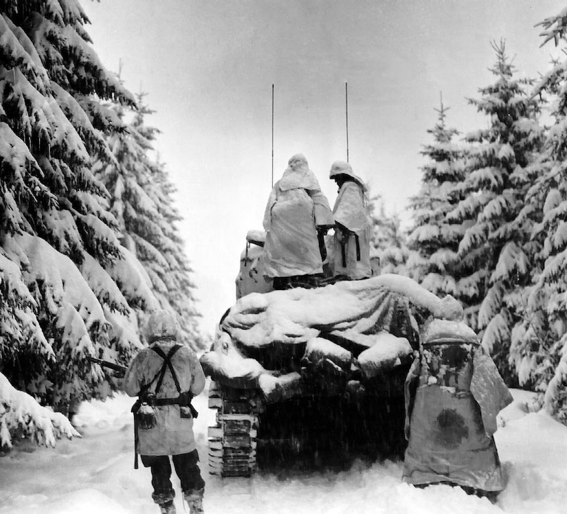 Two soldiers in winter clothing stand on top of a tank that's pushing through heavy snow in a forest. Two other soldiers stand on the ground behind the tank.