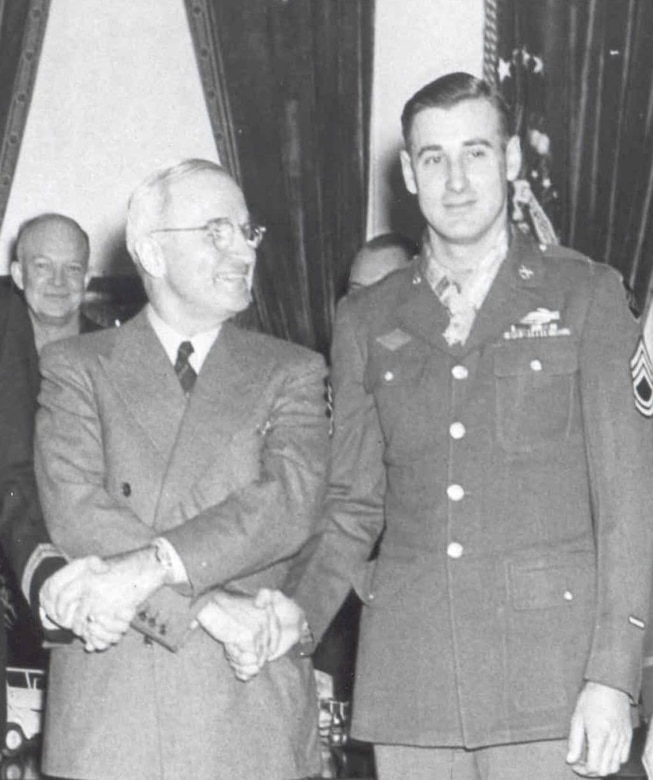President Harry S. Truman, left, stands holding hands with and looking at a soldier to his left, who is wearing a Medal of Honor around his neck. Army Gen. Dwight D. Eisenhower is smiling in the background.