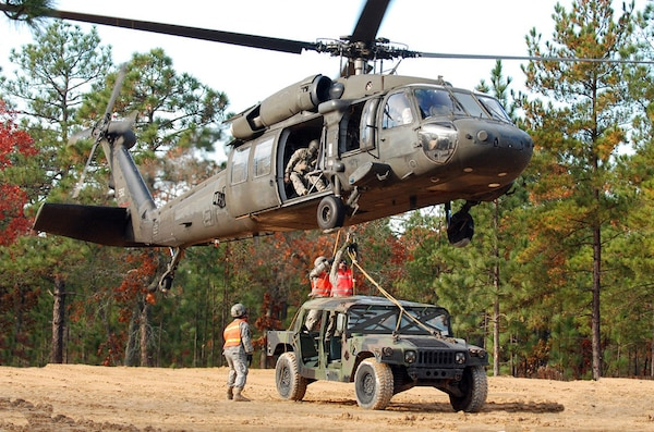 Two paratroopers from the 407th Brigade Support Battalion, 2nd Brigade Combat Team, 82nd Airborne Division, attach a Humvee by harness to the bottom of a UH-60 Black Hawk helicopter during sling load training on Nov. 17. Sling load is a technique used to quickly move supplies from one area to another by helicopter.