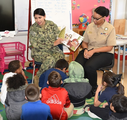 Petty Officer 2nd Class Angelica Brown (left), community service coordinator assigned to Navy Recruiting District San Antonio, joined by NRD-SA's assistant command career counselor, Petty Officer 1st Class Kamitria Delaney, reads to a first-grade class at Dorie Miller Elementary School as part of the school's annual Pearl Harbor and Dorie Miller Remembrance Program.