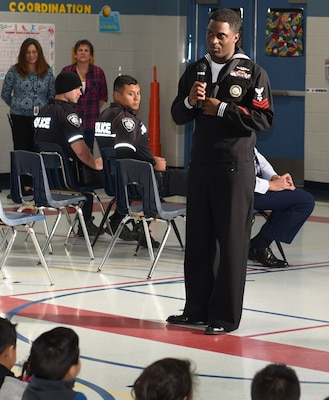 Petty Officer 1st Class Shomari Cooper, assigned to Navy Recruiting District San Antonio, speaks with students of Dorie Miller Elementary during the school's annual Pearl Harbor and Dorie Miller Remembrance Program.  The event was held in remembrance of those who fought and for those who lost their lives Dec. 7, 1941.
