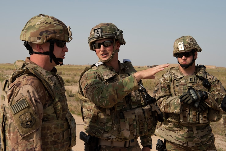 Tech. Sgt. Austin Feenstra (center), 386th Expeditionary Security Forces Squadron member and South Dakota National Guardsman, and Capt. Cooper Emmons (right), 386th ESFS forward team commander, brief Chief Master Sgt. Kenneth Broughman, 386th ESFS, on airfield security operations at Al Taqaddum Air Base, Iraq, April 10, 2019.