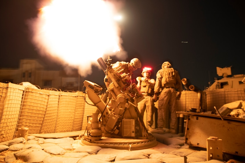 Service members fire a weapon at night. The explosion lights up the area.