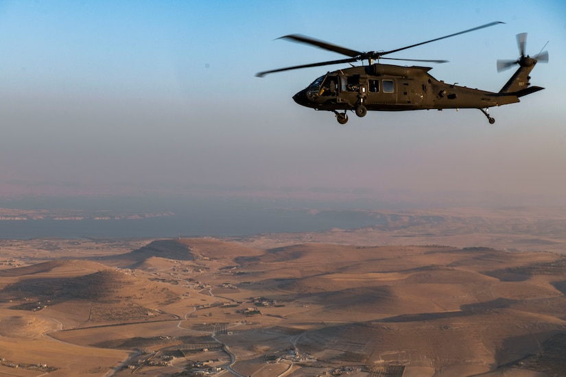 A helicopter flies over a desert.