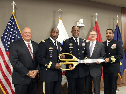 The ceremonial scissors used during the ribbon cutting for Building 45 were signed by (pictured left to right) Yogi Mangual, former Defense Logistics Agency Troop Support commander, Army Lt. Gen. Darrell Williams, director of the Defense Logistics Agency, Army Brig. Gen. Gavin Lawrence, commander of Defense Logistics Agency Troop Support; Richard Ellis, deputy commander of Defense Logistics Agency Troop Support; and Navy Capt. Preston Gill, commanding officer of Naval Support Activity Mechanicsburg. The ceremony was held on Dec. 10, 2019 at the Defense Logistics Agency Troop Support headquarters in Philadelphia. (Photo by Nancy Benecki)