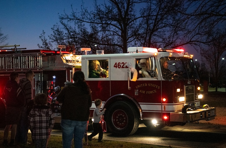 Santa and Mrs. Clause wave at children from a firetruck