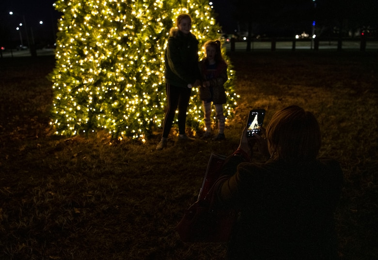 Mom takes a photo of her children by a lighted tree
