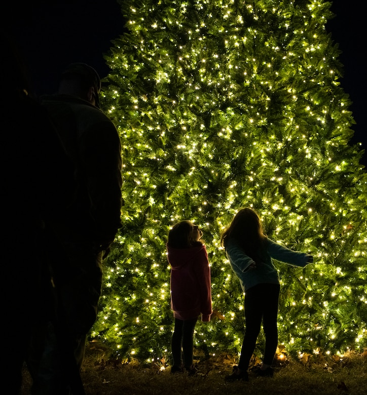 Girls dance by a lighted tree