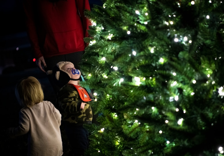 A little boy stares up to the top of a lighted tree