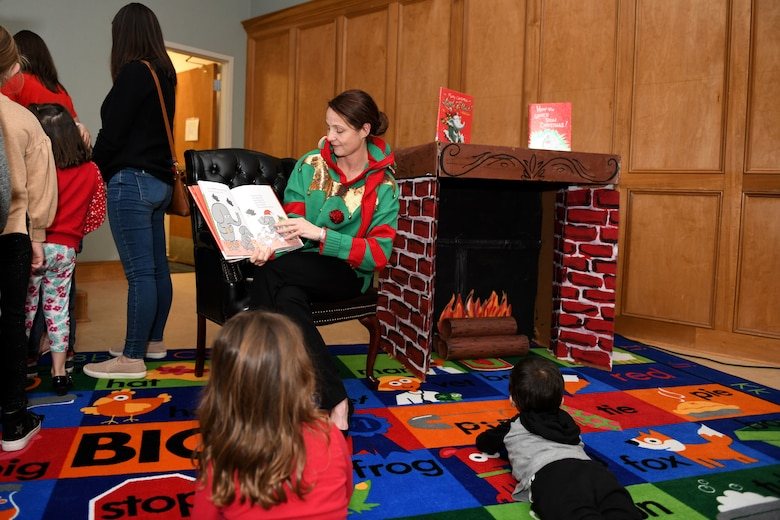a woman reads a book to children
