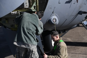 An Airman looks at a computer as another Airman fixes a part of a C-130J Super Hercules.